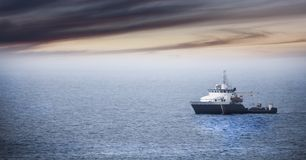 Homecoming: Tired fishermans ship approaching after a hard day.  royalty free stock images