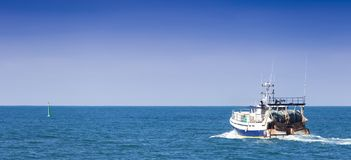 Homecoming: Tired fishermans ship approaching after a hard day.  royalty free stock image