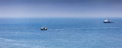 Homecoming: Tired fishermans ship approaching after a hard day.  stock image