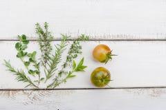 Homegrown örtar och tomater på lantligt wood bräde arkivfoton