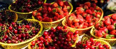 Homegrown μούρα Τα κεράσια και οι φράουλες στα καλάθια για πωλούν Αγροτική αγορά Κόκκινα ώριμα μούρα θερινών συγκομιδών juicy στοκ φωτογραφία με δικαίωμα ελεύθερης χρήσης