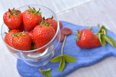 Homegrown, big, aromatic strawberries in transparent dish on foreground close up. Homegrown, big, aromatic strawberries in transparent dish on blue board on Stock Images
