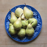 Homegrown Green Pears on a Blue and White China Plate. An arrangement of fresh picked pairs on an antique china plate Royalty Free Stock Photos