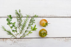 Homegrown herbs and tomatoes on rustic wood board Stock Photos