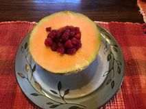 Homegrown Melon and Raspberries. Home grown cantaloupe with fresh picked raspberries for breakfast Royalty Free Stock Photography