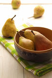 Homegrown pears from rural garden. In bowl over on napkin and wooden table. Vertical image stock images