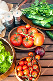 Homegrown vegetables in wooden dishware for spring picnic. Royalty Free Stock Images