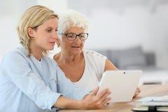 Homehelper при пожилая женщина используя таблетку Стоковая Фотография