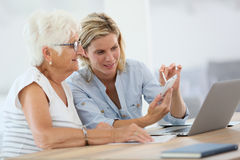 Homehelper with elderly using electronical devices Stock Image