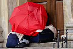 Homeless. Person in the city sleeping under umbrella on suitcase with personal belongings Royalty Free Stock Photos