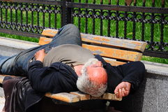 Homeless. A senior homeless man sleeping on bench Royalty Free Stock Images