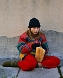 Homeless. Girl - child (beggar) sitting on the cold floor without shoes (barefoot - socks), dirty in the face with a black hat and gloves and eat bread Royalty Free Stock Photo