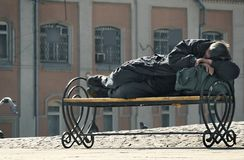Homeless. The homeless sleeps on a bench in beams of the morning sun stock photo