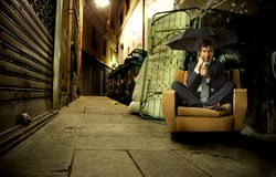 Homeless. Businessman with umbrella sitting on armchair in a city street Royalty Free Stock Photo
