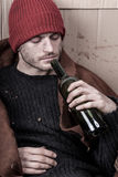Homeless addicted to alcohol. Homeless man addicted to alcohol on the street Stock Images