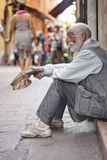 Homeless asking for help. BOLOGNA - JUNE 2012- A homeless old man beggar sitting on the street and asking for help on May 14, 2011 in BOLOGNA, Italy royalty free stock photography