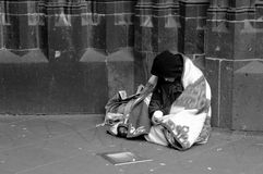 Homeless b/w. Homeless man sitting in front of a church and begging for money stock photography