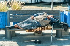 Homeless barefooted woman sleep on the wooden bench on urban street in the city on the sidewalk.  stock images