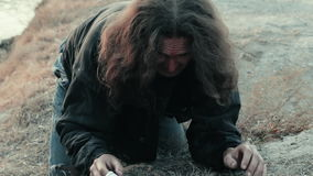A homeless beggar found the paper document chance near the river. Bleeding. God`s help stock video footage