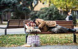 Homeless beggar man with a bag lying on bench outdoors in city, sleeping. A homeless beggar man with a bag lying on bench outdoors in city, sleeping. Copy space stock photography
