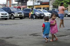 Homeless beggar`s children boy and girl, walking, take care of each other at church yard. San Pablo City, Laguna, Philippines - January 6, 2017: homeless beggar` Stock Image