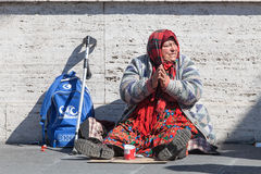 Homeless beggar. Woman asking for alms. Street. Rome Italy. An elderly woman with her hands folded in prayer is sitting in the middle of the street to royalty free stock images