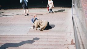 Homeless beggar woman begging at the entrance to the subway. Social distress stock footage