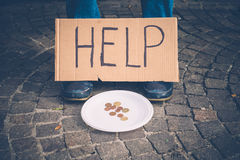 A homeless begging money because poor. With cartel Stock Image