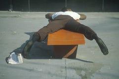 Homeless black man sleeping on a park bench, New York City, New York Stock Images