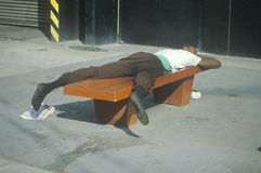 Homeless black man sleeping on a park bench, New York City, New York Stock Photo