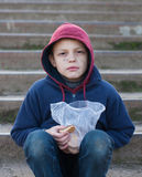Homeless boy eats cookies Royalty Free Stock Photos