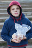 Homeless boy eats cookies Stock Images