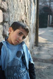 Homeless boy with his home patterned sweather. Standing near a wall and missing a warm home Stock Images