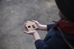 Homeless boy holding a cardboard house. Dirty hand Royalty Free Stock Photos