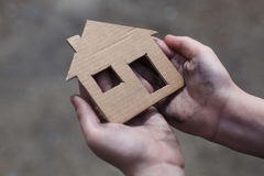 Homeless boy holding a cardboard house Stock Photography