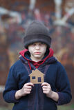 Homeless boy holding a cardboard house Stock Photos