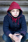 Homeless boy holding a cup Royalty Free Stock Photo