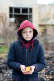 Homeless boy holds cookies in hand Stock Photos