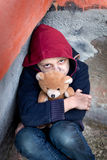 Homeless boy leaned against the wall with bear Royalty Free Stock Image