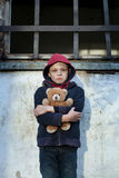Homeless boy leaned against the wall with bear Royalty Free Stock Photo