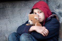 Homeless boy leaned against the wall with bear Royalty Free Stock Photos