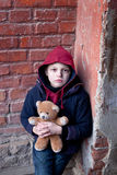 Homeless boy leaned against the wall with bear Stock Photography