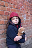 Homeless boy leaned against the wall with bear Stock Photo