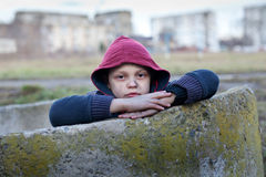 Homeless boy leaned against the wall Royalty Free Stock Photo