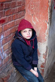Homeless boy leaned against the wall Royalty Free Stock Photography