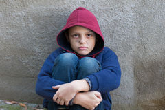 Homeless boy leaned against the wall Royalty Free Stock Image