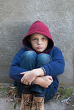 Homeless boy leaned against the wall Royalty Free Stock Photos