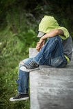 A homeless boy sits on a bench with her head bowed down. Portrait Royalty Free Stock Image