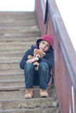 Homeless boy sitting on the bridge Stock Photo