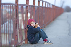 Homeless boy sitting on the bridge Royalty Free Stock Photo